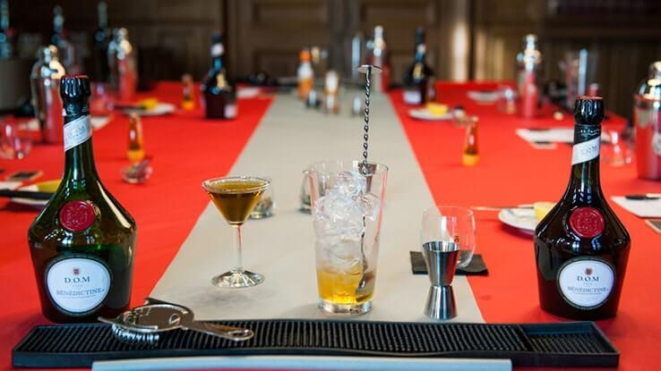 Verre rempli de glace et de Bénédictine. Deux bouteilles de Bénédictine de chaque côté du verre.